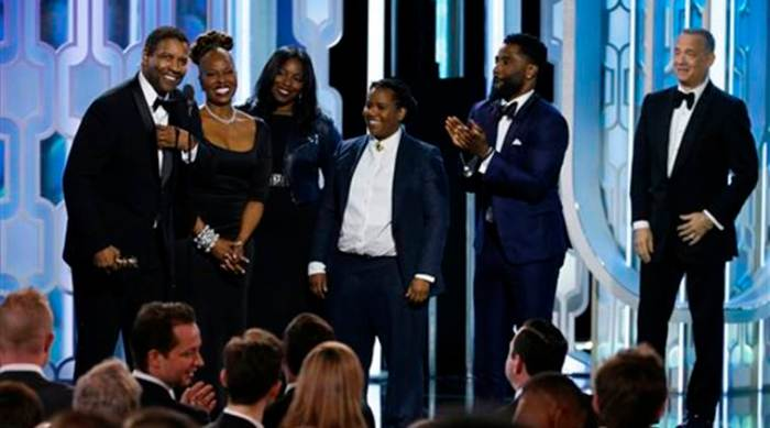 In this image released by NBC, Denzel Washington, left, stands with his wife Pauletta, second left, and his family as he accepts the Cecil B. Demille Award at the 73rd Annual Golden Globe Awards at the Beverly Hilton Hotel in Beverly Hills, Calif., on Sunday, Jan. 10, 2016. (Paul Drinkwater/NBC via AP)